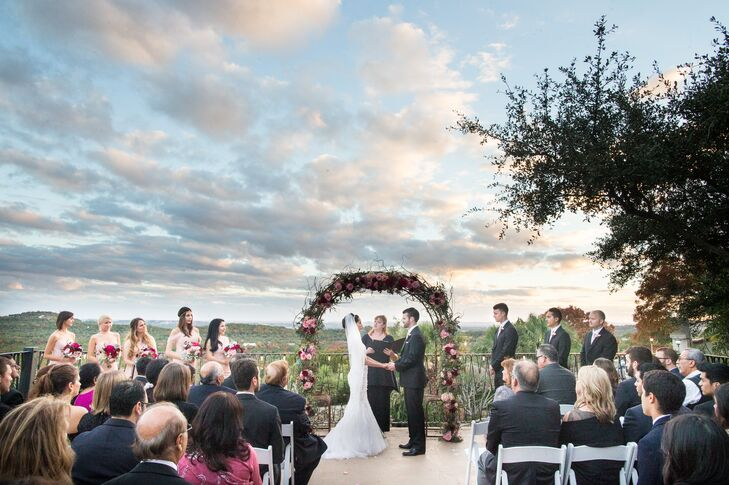 The bride and groom read poems to one another at the ceremony, which took place on a terrace overlooking the Texas Hill Country. The wedding arch included jewel-toned blooms with wild berries and curly willow.