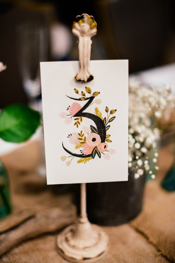 To help guests find the way to their seats, Noelle and Patrick labeled each of the tables with hand-painted floral table numbers, which they displayed on vintage-inspired pedestals. The numbers tied in seamlessly with the decor's romantic, bohemian vibe.