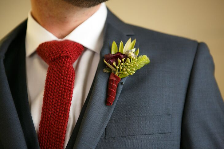 Jackson wore a gray suit with a red knit tie. His boutonniere had a single red rose with greenery,  with a red velvet boutonniere wrap to complete his winter style.