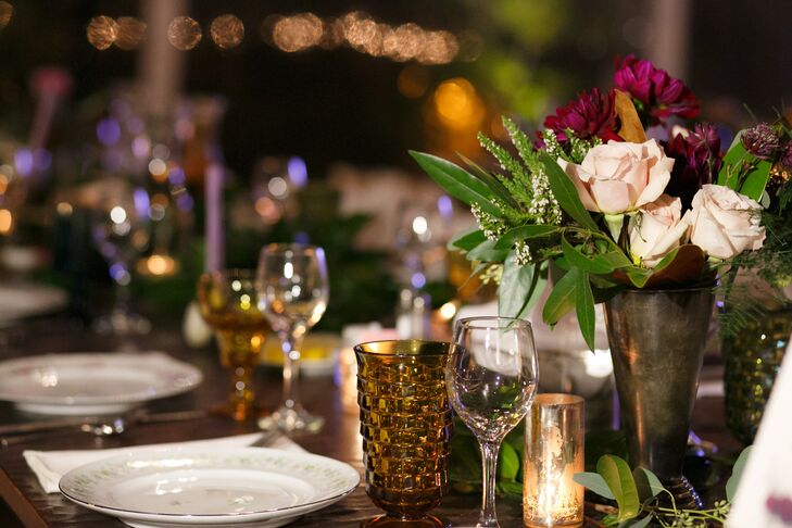 The farm tables hosted mismatched china flatware and colorful goblets at each place setting. Centerpieces included winter flower arrangements in rich purple, red, blush and white hues with greenery, metallic vases and mercury glass votives.