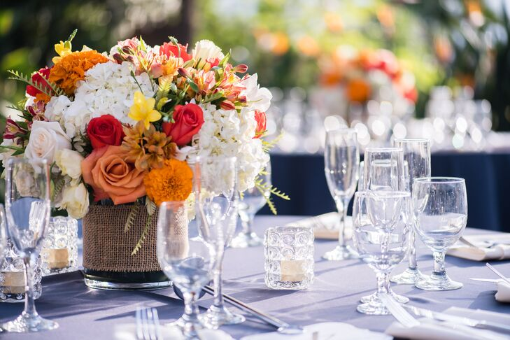 Clear Glass Goblets and Champagne Flutes with Orange and Red Floral Centerpiece
