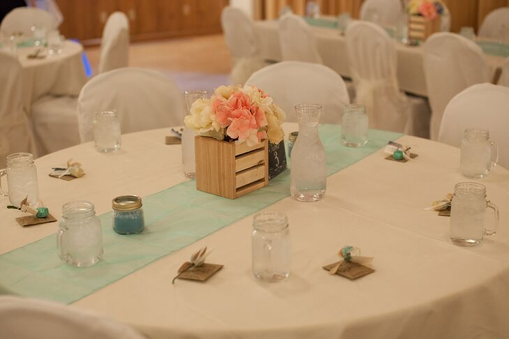 Melissa and Dustin chose a playful pink, ivory and mint color palette for the reception, both giving the Silverthorne Town Pavilion a cheerful vibe, while tying into the wedding's vintage theme. The couple decorated the reception tables with pale mint table runners and arrangements of fabric flowers displayed in small wooden crate vases, which Melissa handcrafted herself.