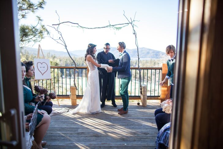 Sara held Debora's hands at the branch wedding arch during the ceremony, where she sported her navy blue jacket and emerald green pants that blended in with the outdoor elements.