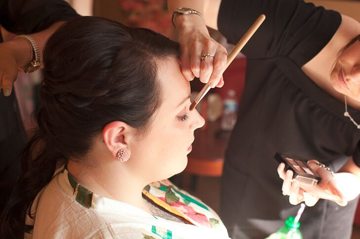The bride is covered in stunning tattoos and wanted them to be the focus of her wedding look, so she only accessorized minimally with a simple infinity necklace and a pair of chrysanthemum gauges from Etsy. She paired them with natural-looking makeup and a somewhat vintage-inspired updo to match the style of her wedding dress.