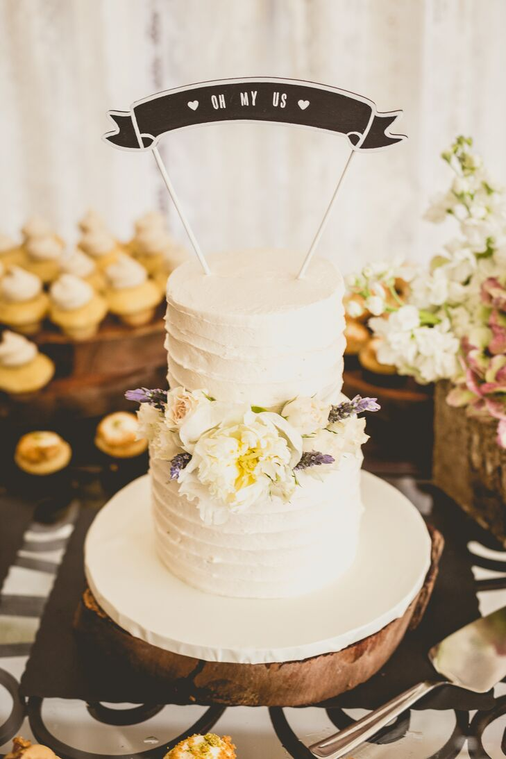 On top of personalized mini cupcakes, Roxy and Rodney also served a two-tier, ivory buttercream confection from Drea's Desserts. The center was highlighted with a white peony to match their arrangements as well as white roses and lavender from Flowers International Events.