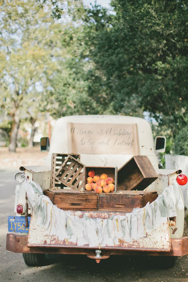 Playful vintage props were scattered throughout the property to add old world charm to the wedding's laid-back feel. A vintage truck decked out with festive bunting and wooden crates filled with bright fresh peaches greeted guests as they arrived to the ceremony.