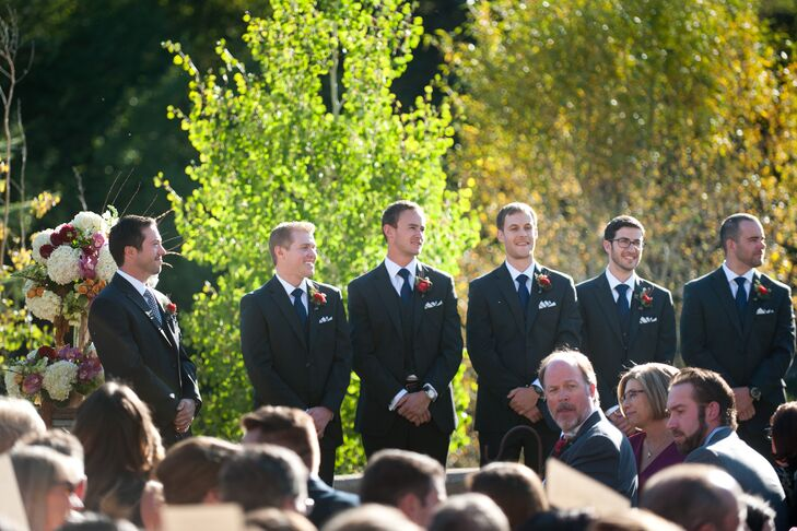 The groomsmen wore three-piece charcoal suits with navy ties and white and navy pocket squares. The groom's tie was blue and white polka dots to differentiate himself.rn