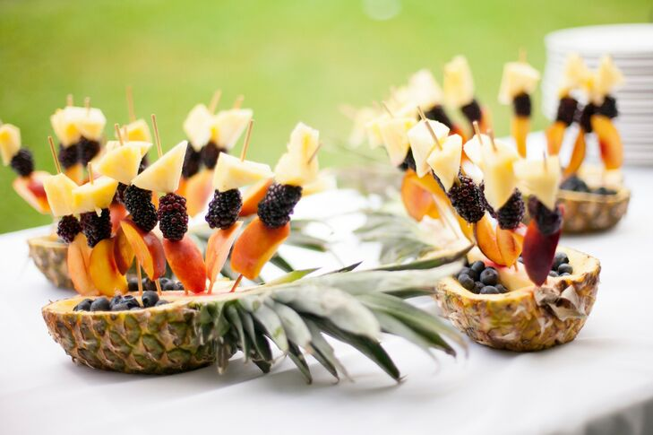 Fresh fruit kabobs were displayed in sliced pineapples and offered to guests.