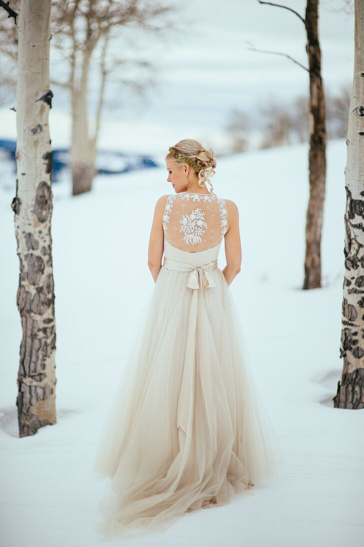 Suzi wore designer Catherine Deane's Onyx gown for her winter nuptials. She loved the flowing tulle skirt and the white lace detailing on the back. She completed her look with a champagne satin belt and a wintery green and gold flower crown.