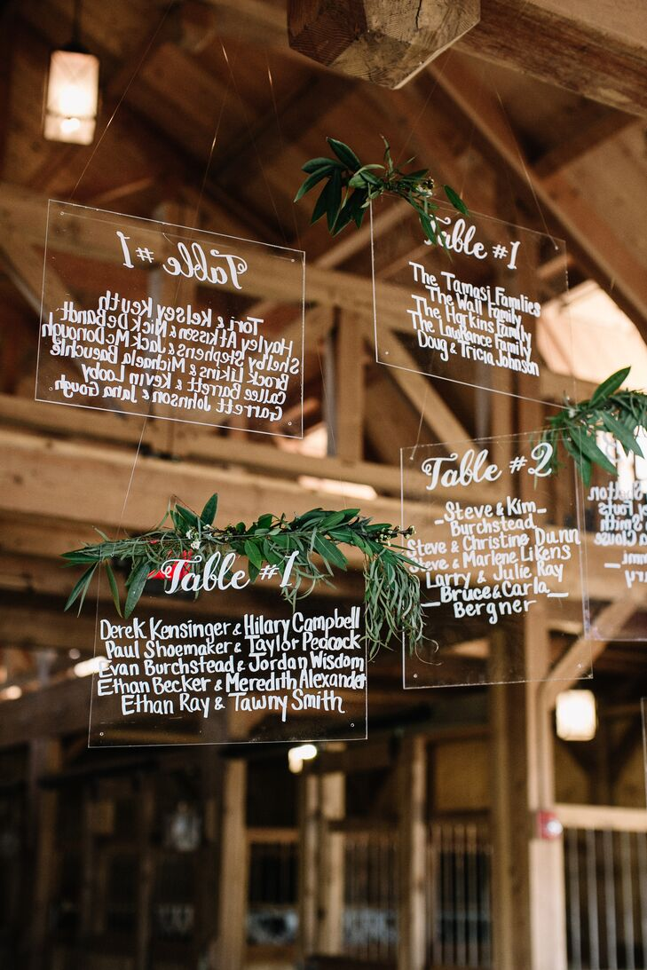 "Midway through the planning process, Hope decided that the decor was in need of a few modern touches. ""Our seating signage was a random idea of mine that I really didn't think would become a reality, but with Ultra Pom and Jonnelle of Events by Elle, it did,"" Hope says. ""I'm still obsessed."" The names of guests were hand lettered onto squares of clear acrylic material, which were then draped in garlands of greenery and suspended from the rafters of the barn."