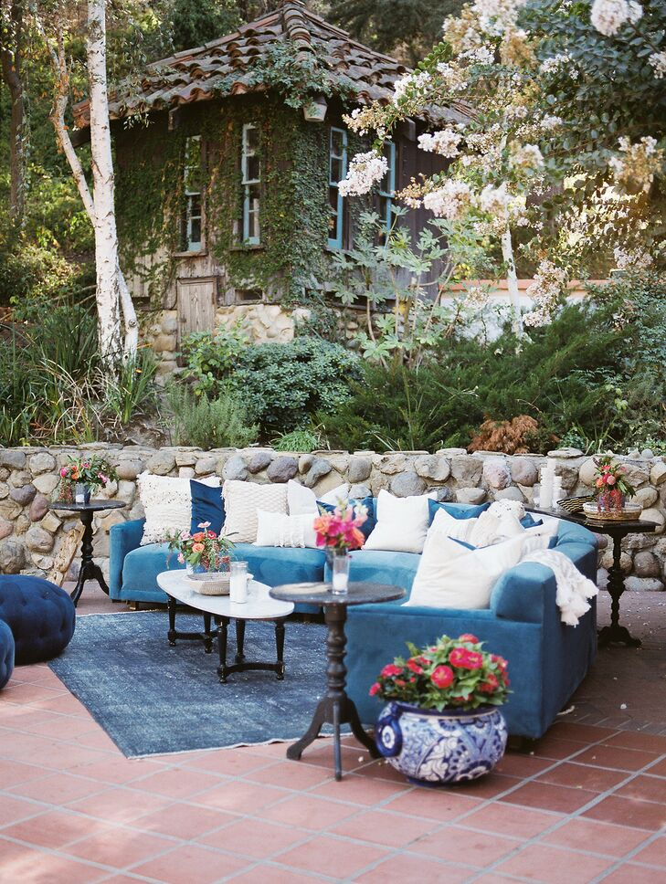 Spanish-Style Outdoor Lounge Area with Blue Couches and Throw Pillows