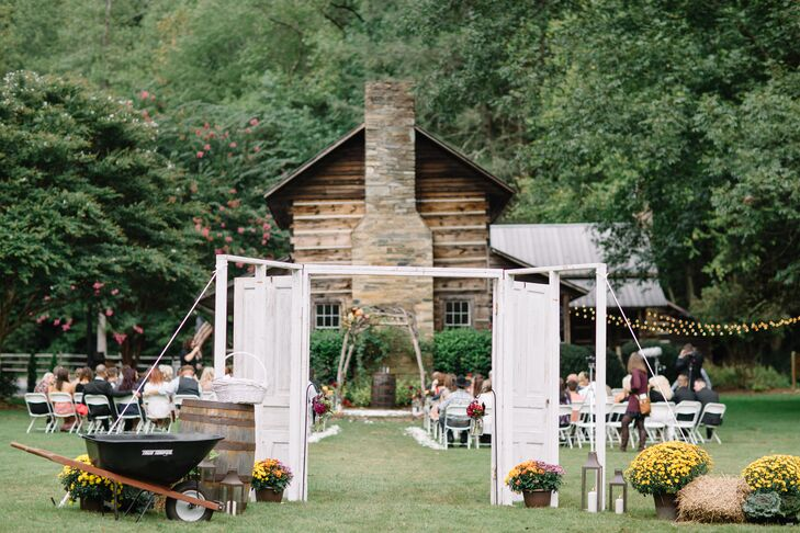 "Katie walked down a white-rose-petal aisle to a rustic log-and-stone cabin. ""On the stone area where we stood, there were two trios of different-size lanterns with candles on the ground, and they were surrounded with flowers,"" she says. White chairs and shepherd hooks with hanging jars of flowers lined the center aisle."