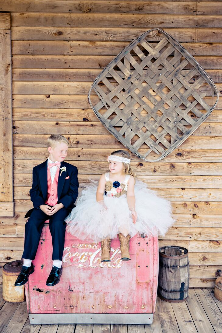 Samantha and Chris's little attendants dressed the part, and they were too cute! The flower girl wore a tulle dress with burlap, coral and navy floral appliques, a lace headband and cowboy boots. The ring bearer dressed up in a navy suit with a coral vest and bow tie.