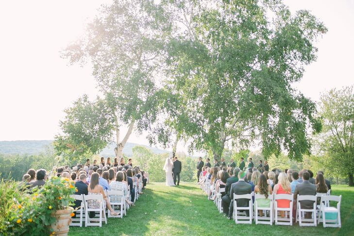 "Before kicking off the festivities, Kimberly and Peter said ""I do"" in an outdoor ceremony overlooking hundreds of acres of lush forest, quaint ponds and rolling hills. Two majestic birch trees framed the pair as they exchanged vows, and petite arrangements of baby's breath dotted the aisle."