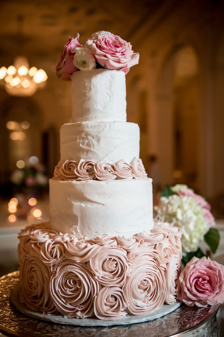 Confection Perfection created this four-tier wedding cake with blush rosettes for a romantic twist on a classic design. Fresh white and pink flowers topped the design.