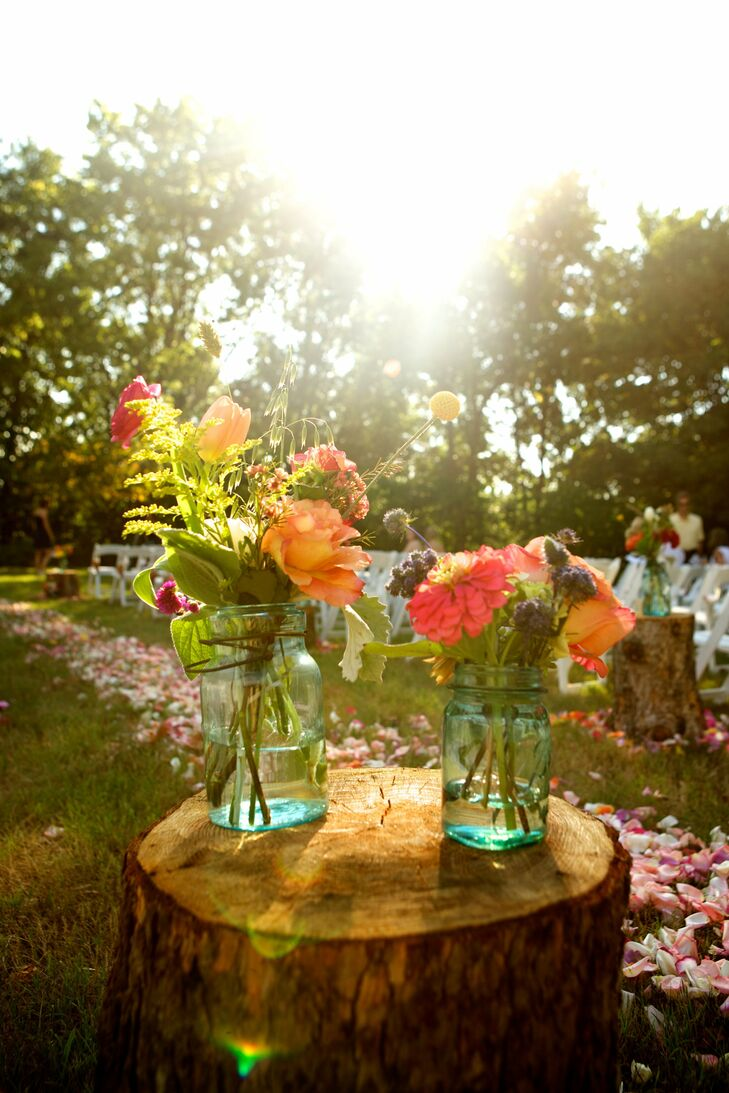 The aisle was lined with rose petals and stumps adorned with turquoise mason jars filled with wildflowers.