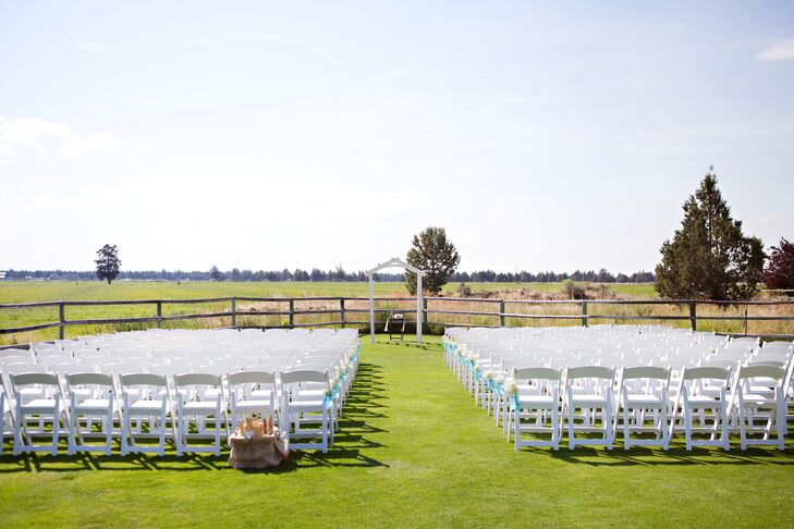 """""""We were blessed with an already beautiful location, with very little we had to do to decorate,"""" the couple says. """"We went simple on the aisles with blue mason jars filled with baby's breath. With the landscape of the cascade mountains in the background, it couldn't have been more picturesque."""""""