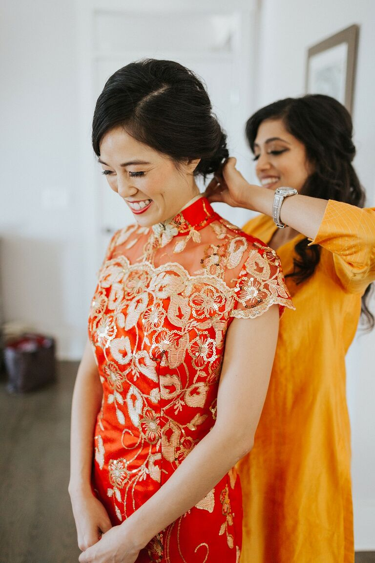 Bride getting dressed in qipao for Chinese wedding