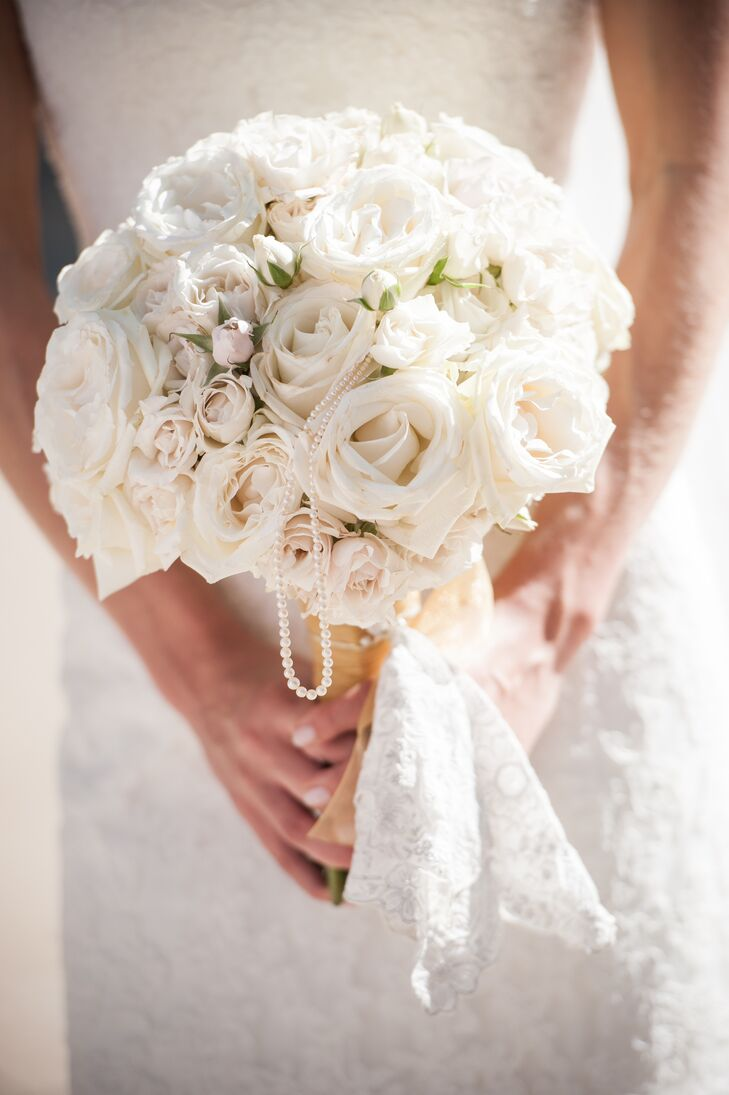 Lisa carried an all-white bouquet with roses that was wrapped in white lace. The bouquet included pearl strands as accents.