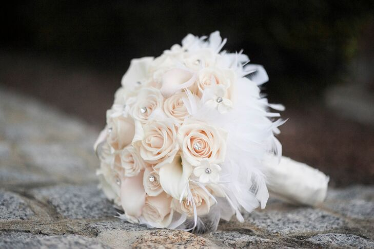 Julie held and all-white bouquet of calla lilies roses with crystals and a feather collar.