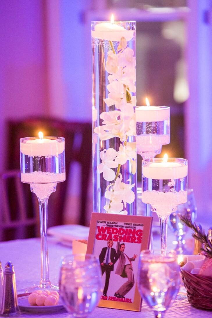 Glass cylinder vases filled with submerged white dendrobium orchids topped a portion of the reception tables.