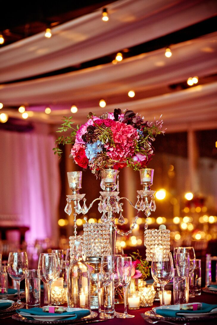 High centerpieces of pink, purple and blue flowers surrounded by votive candles topped the reception tables.