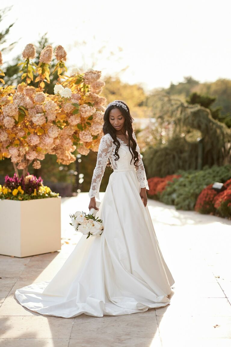 Bride in long-sleeve wedding dress holding white bouquet