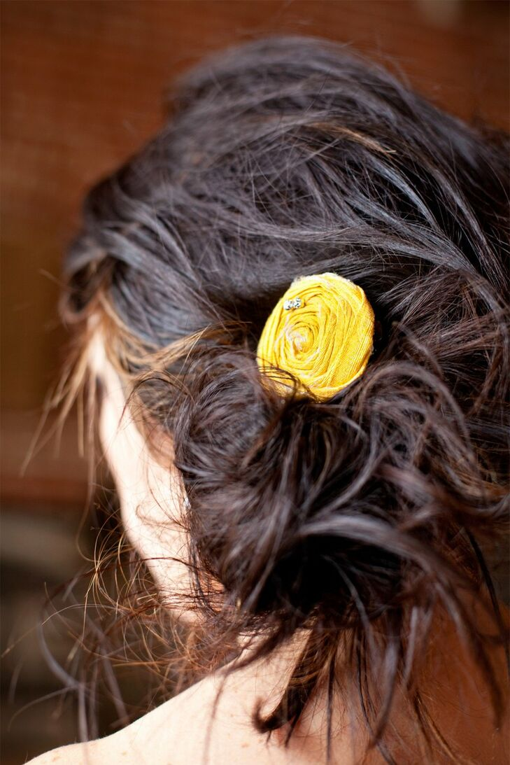 The bride wore her hair to the side with a yellow flower clip for a natural simple look.