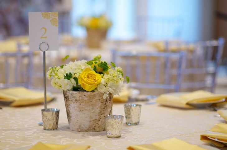 The reception tables were decorated with rustic wooden vases filled with ivory hydrangeas and yellow roses.