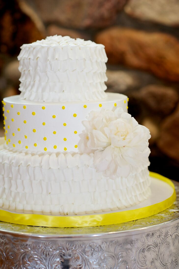 Lauren and Austin enjoyed a three-tier white fondant wedding cake with two ruffled layers and a center layer adorned with yellow polka dots.