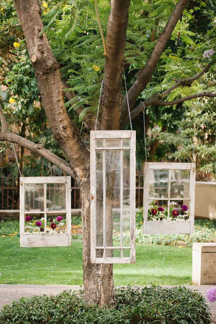 In lieu of an alter, the couple chose to hang vintage windows with flower boxes as the focal point of the ceremony.