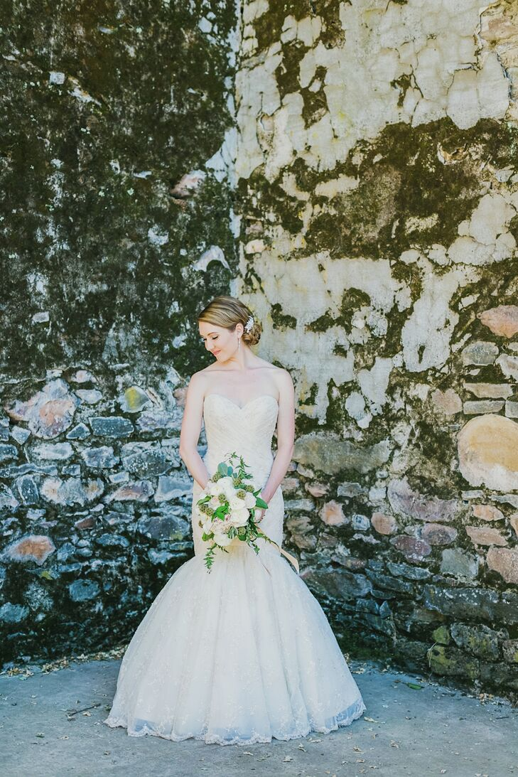 "Emily's Ramona Keveza strapless trumpet-style silhouette gown was elegant but with naturalistic textures that suited the sunny outdoor setting. Made from English netting and adorned with delicate beading throughout, the gown's beautiful train added some drama and romance. ""I paired it with a simple veil embellished by tiny crystals along the seam and rose-colored Valentino kitten heels in lace with a bow,"" Emily says."