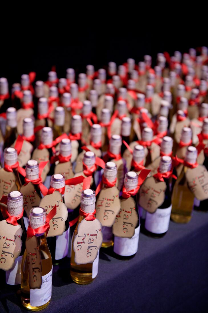 "As favors, Nicole and Daniel gave their guests bottles of red and white wine that were made and bottled by Nicole's father. The bottles had tags that read ""Take me,"" to go with the 'Alice in Wonderland' theme."