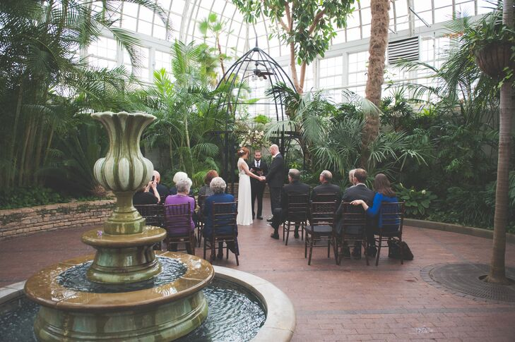 Rebecca and Derik held hands at the front of the ceremonial altar as guests watched their marriage take place in the Palm House at Franklin Park Conservatory.