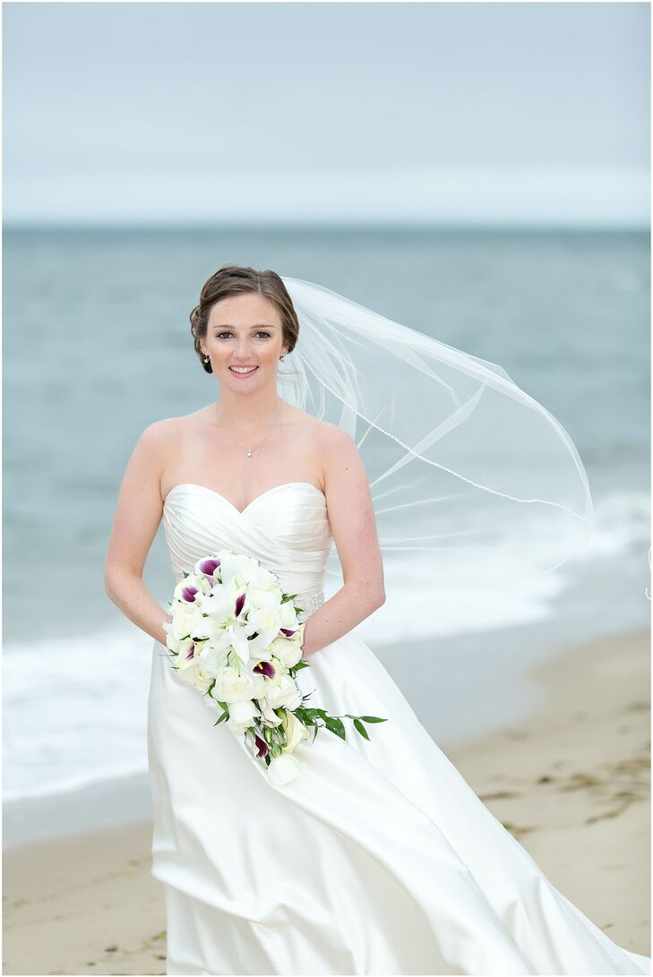 "Carrie walked down the aisle in a classic A-Line gown by Allure Bridal. The dress featured a draped sweetheart bodice and full satin skirt. ""The skirt was a little fuller than I would have liked when I originally bought it,"" says Carrie, ""so I had my seamstress remove one of the layers underneath to bring down the pouf a little."""