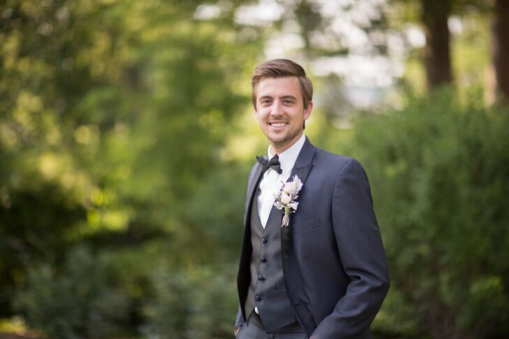 Nate wore a dark gray tuxedo with a black bow tie and vest. His white boutonniere consisted of white roses and dusty miller.