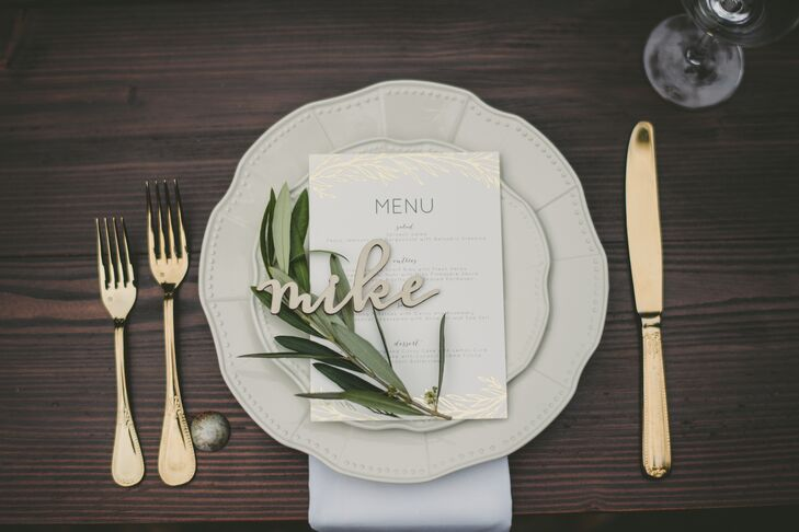 Gold flatware accompanied vintage-style ivory plates at each table setting, along with personalized name plates that Crystal had cut from wood.