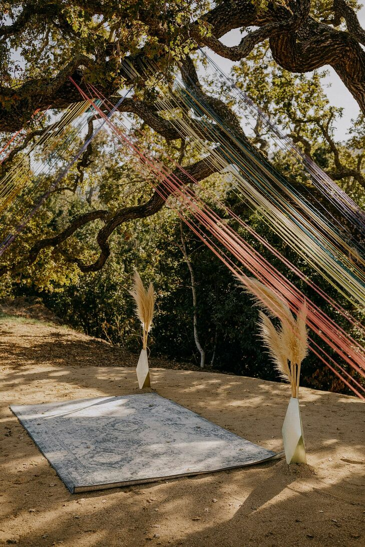 Whimsical Outdoor Ceremony Site with Rug, Grasses and Rainbow Art Installation