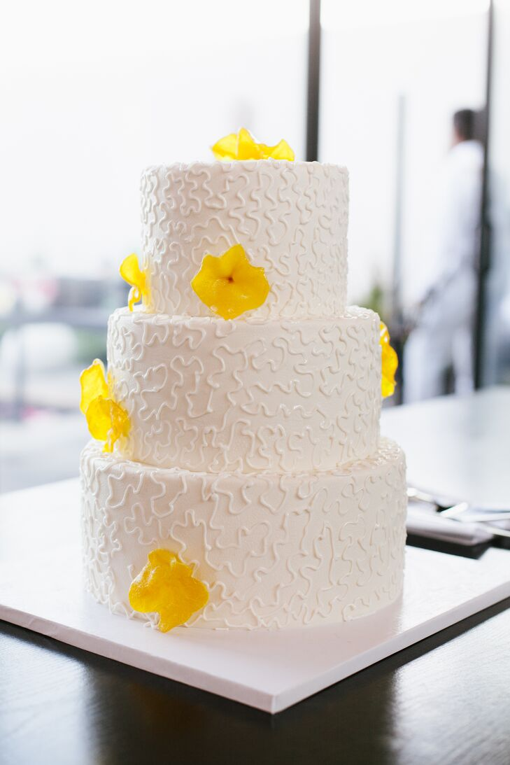 Mango-colored sugar flowers dotted the modern, white wedding cake.