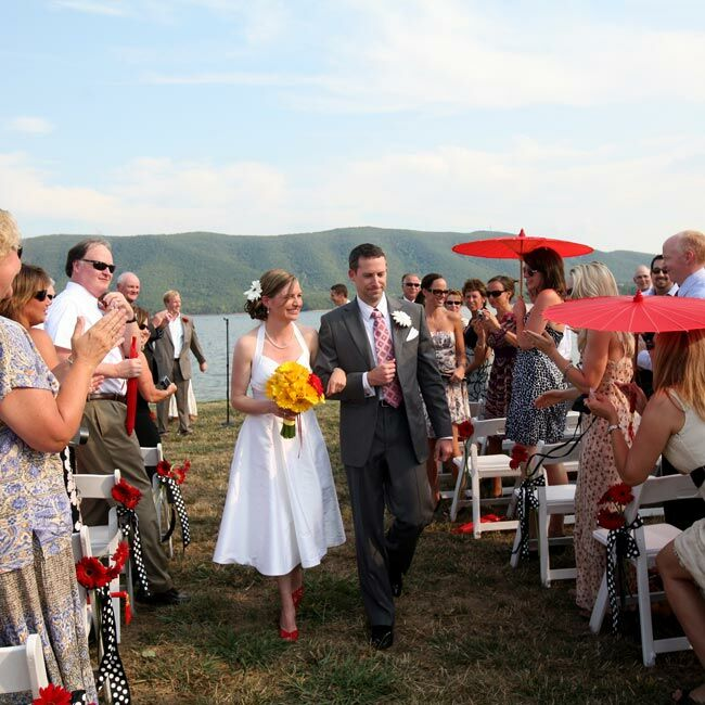 The couple personalized their waterfront ceremony site with black-and-white polka-dotted chair ties adorned with red gerbera daisies. Red parasols brought in more of the signature hue and helped shield guests from the sun.