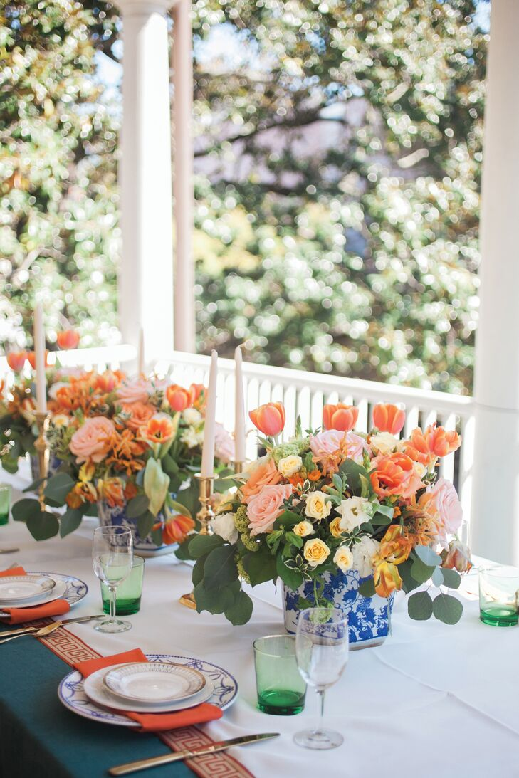 Hunter-green linens topped each dining table along with antique brass candlesticks, parrot tulips in Chinoiserie vases and thick ivory table runners, hand-sewn by Matthew's mother.