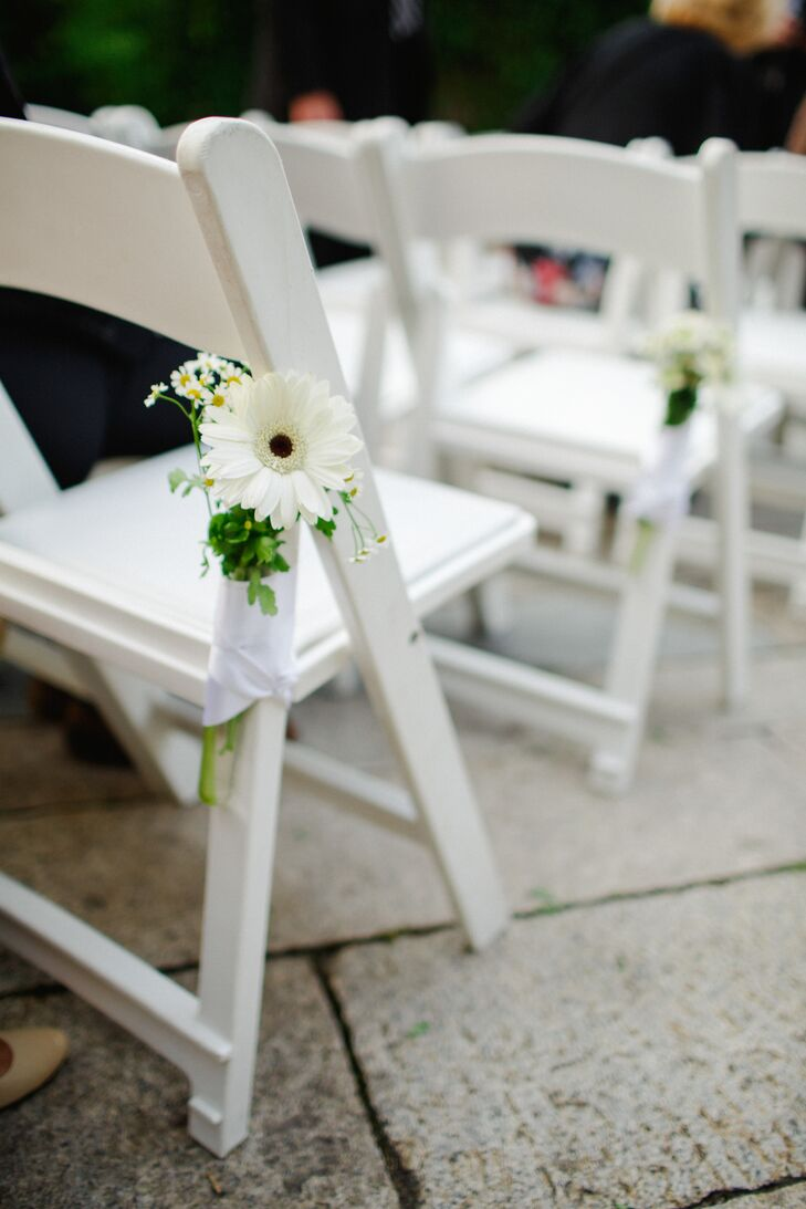 In addition to the colorful ribbon backdrop created for the ceremony by the couple's coordinator, Jove Meyer, the couple decorated the outdoor ceremony space at the Foundry in Long Island City, New York, with understated, yet playful bunches of white gerbera daisies and wax flowers. The small bouquets were added to the end of each row, tied together with lengths of white ribbon.