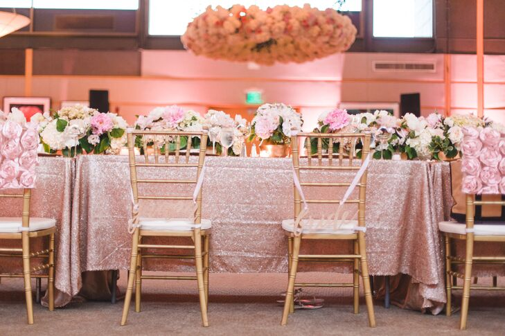 A sparkly blush tablecloth covered the head table. Lush peonies lining the center of the table matched the pink rosettes on the backs of the gold chiavari chairs.