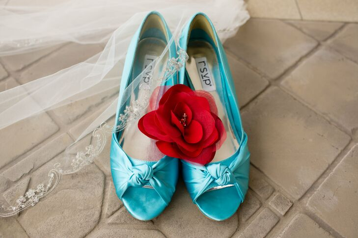 Teal open toed shoes worn by the bride were decorated with a red rose with a veil draped over the corner.