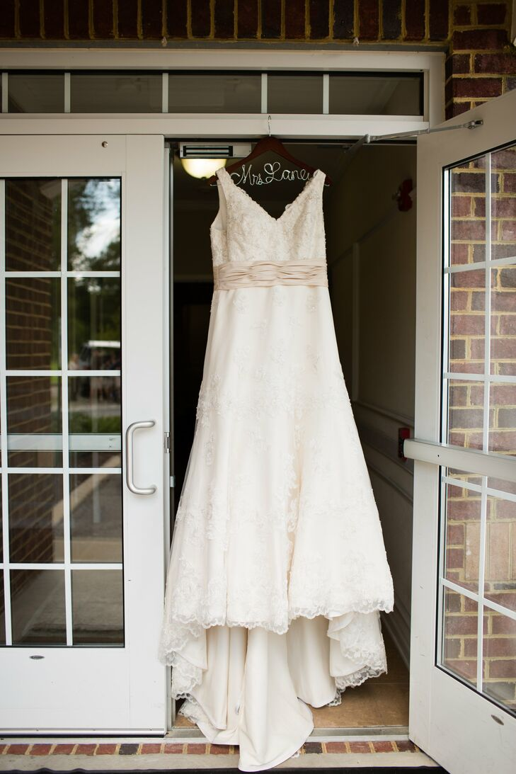 The bride wore a champagne wedding dress designed by Alfred Angelo with a v-neck going down the front and back. The sheer laced top layer of the dress had subtle beading and a small train.