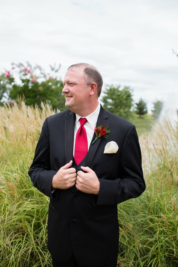 Chris wore a classic black tuxedo with a red tie and a red alstroemeria boutonniere pinned to his jacket above his ivory pocket square.