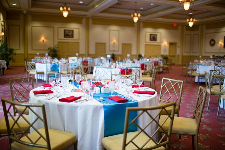Dining tables at the reception were dressed in white tablecloths with teal table runners, accents with red napkins.