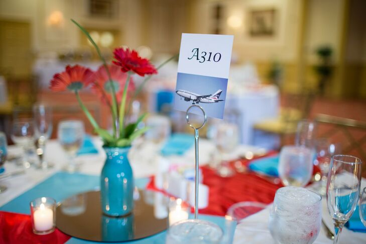 A white card with an airplane model number was used to mark reception tables for guests to match their escort cards with. The card was positioned next to a red daisy assortment in a teal vase.