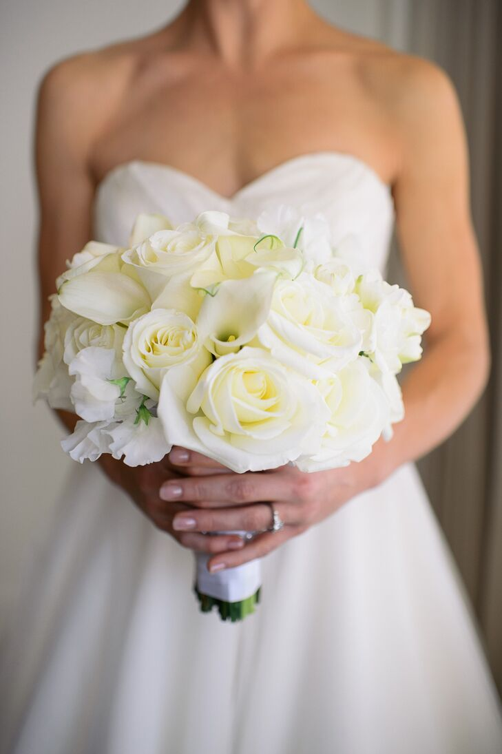Joan carried a simple ivory bridal bouquet made up of roses, calla lilies and stock flowers. The all-white bouquet echoed the monochromatic flower arrangements at the reception. All of the gorgeous floral arrangements at Joan and Jon's wedding were created by Blue Vanda Designs, a floral design studio based out of Bowie, Maryland.
