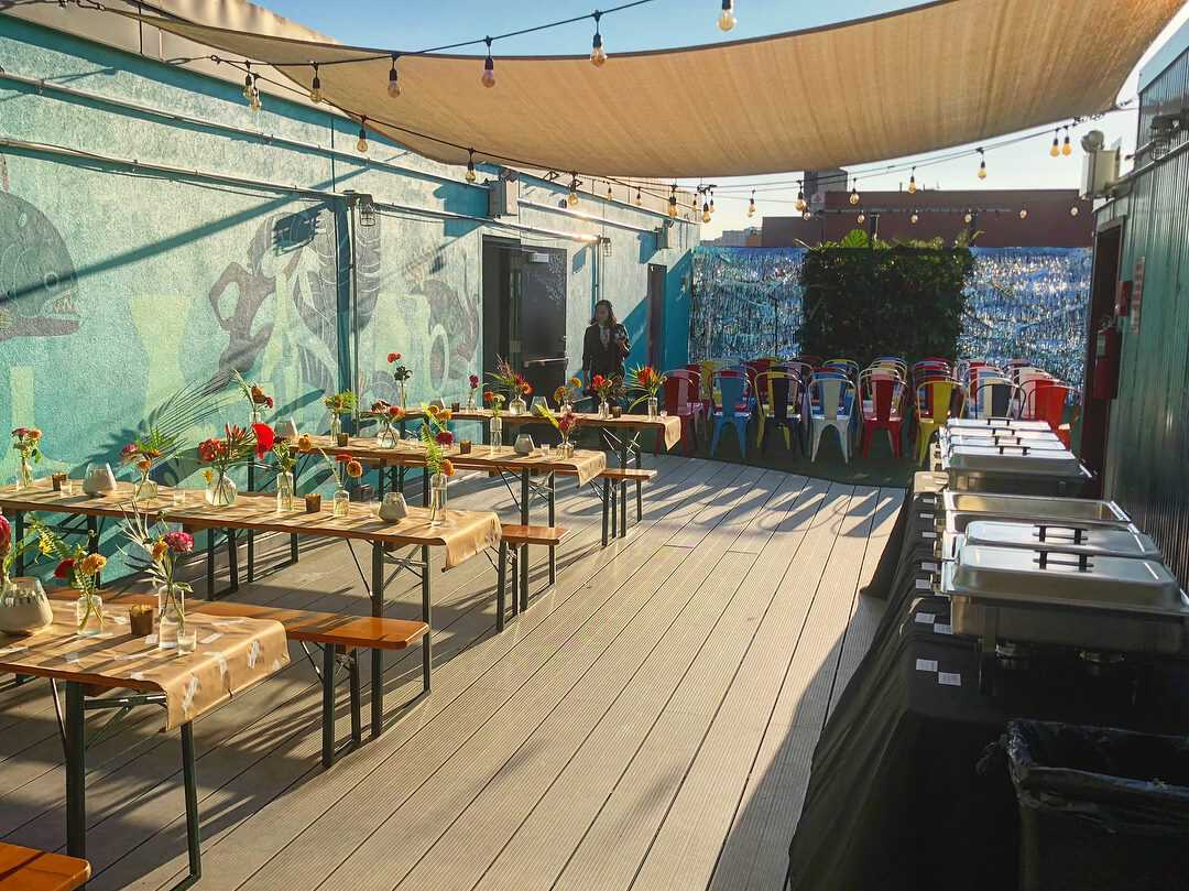 view of our wicked lady rooftop bar with picnic tables and summery deck space